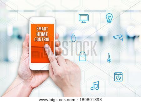 Hand Holding Mobile Phone With Smart Home Control With Feature Icon On White Blurred Background, Dig