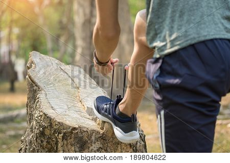Cropped shot of young man runner tightening running shoe laces getting ready for jogging exercise outdoors. Male jogger lacing his sneakers standing on forest path before morning run.