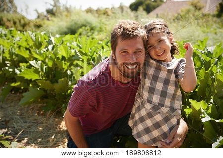 Portrait Of Father And Daughter Standing On Community Allotment