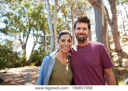 Portrait Of Couple Hiking Along Forest Path Together
