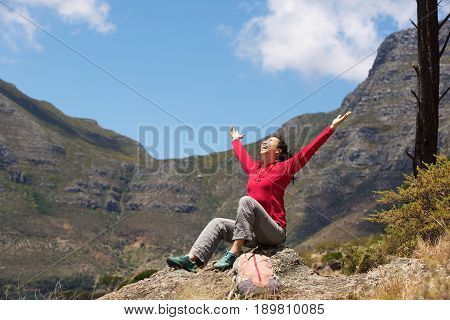 Asian Female Hiker Sitting On The Peak With Arms Raised To The Sky