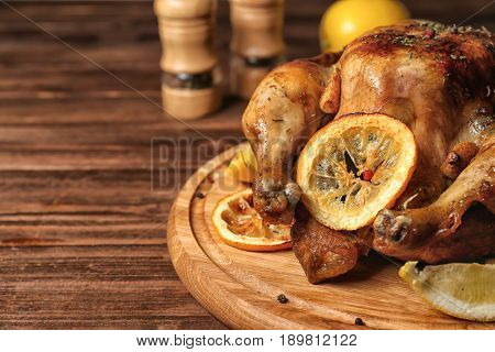 Homemade baked chicken with lemon on wooden board
