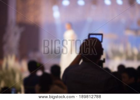 Cameraman recording video of Wedding fair out of focusblur background.