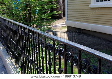 Length of black wrought iron fencing that runs along the  property line of country home.