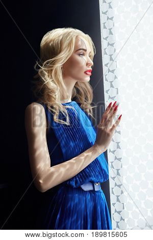 Blonde in blue dress standing at window woman falls shadow of the curtains. Beautiful sensual portrait of a mysterious girl. Shadow from the curtains on girl's face. Bridesmaid in the window