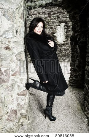 Sexy Lady In Black With Long For Coat And Leather Boots