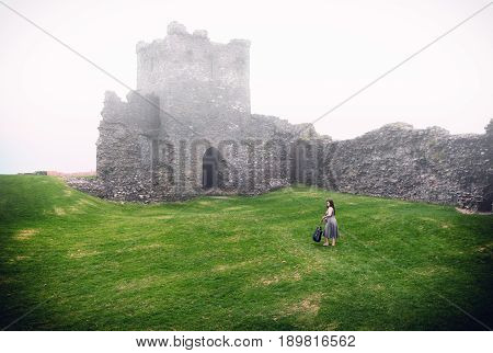 Beautiful Lady With Guitar Walks Across Misty Grass To Forgotten Castle