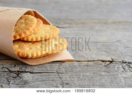 Delicious salty crackers in a wrapping paper on an old wooden background with copy space for text. Savory crackers for kids or adults. Picnic snack idea