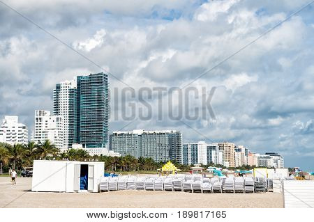 sunbeds stacked on sand beach green palm trees and high rise apartment buildings or hotels on sunny day. miami south beach skyline with white clouds on blue sky. Summer vacation. Urban landscape