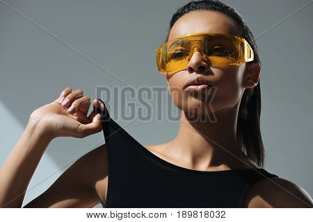 African American Sensual Stylish Model In Black Swimsuit And Protective Goggles Posing On Grey