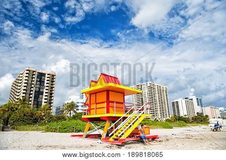 Miami USA - January 10 2016: Miami beach or south beach colorful lifeguard tower wooden station on sandy beach green palms high rise buildings on sunny cloudy blue sky. Summer vacation. Safety