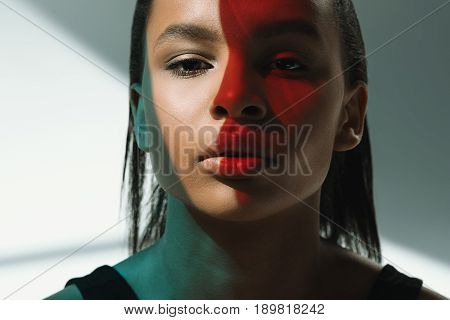 Portrait Of African American Seductive Stylish Model With Red Shadow On Face Looking At Camera