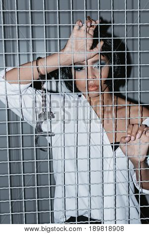 Portrait Of Pensive Woman In Cuffs Standing Behind Grate