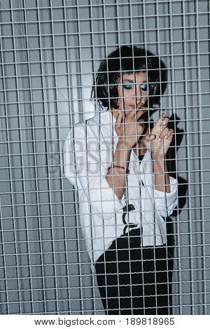 Woman In White Shirt And Cuffs Smoking Cigarette Behind Grate