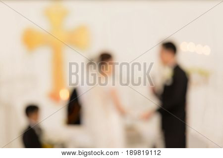 Abstract blurred photo of bride and groom in church during wedding ceremony.