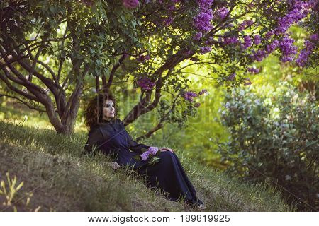 Woman is resting under a bush of blossoming lilacs in the park.