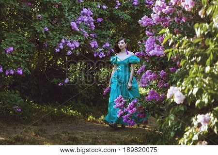 Pretty woman walking in the park blooming lilacs.
