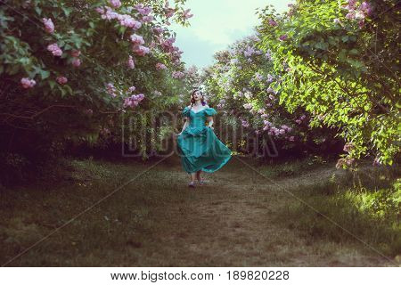 Lovely woman runs through the garden among the flowering trees.