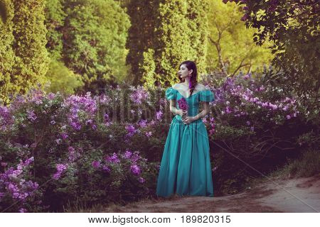 Young woman in lush bushes of lilac she sadly dreams.