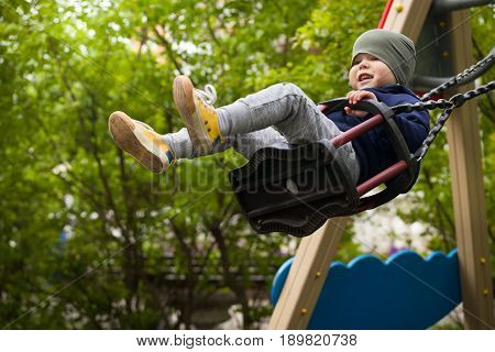 Portrait of adorable little toddler on swing. Happy cheerful smiling cute little kid swinging in park. Playing in nursery area outdoors.