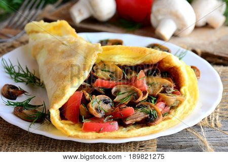 Mushrooms and tomatoes omelette idea. Home omelette stuffed with mushrooms, tomatoes and dill on a plate and vintage wooden table. Vegetarian omelette recipe. Rustic style. Closeup