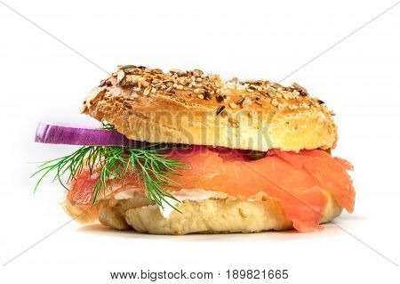 A side view of a bagel with cream cheese, lox, purple onions, capers, and dill, on a white background with a place for text