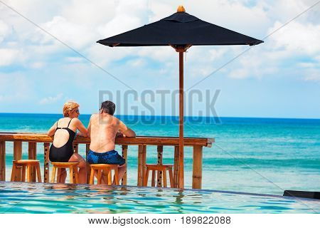 Successful retirement recreation summer vacation concept. Retired mature couple enjoying beautiful sunny day in swimming pool at beach club. Happy senior woman and man sitting at poolside beach bar.
