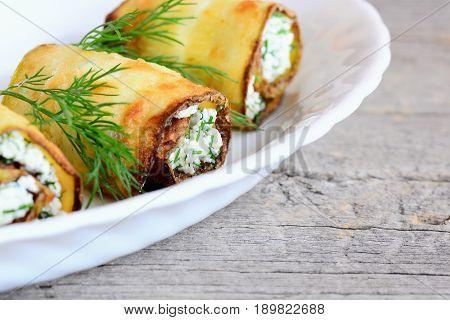 Cottage cheese zucchini rolls. Fried zucchini rolls with cottage cheese and dill on a plate and wooden table. Beautiful vegetarian appetizer recipe
