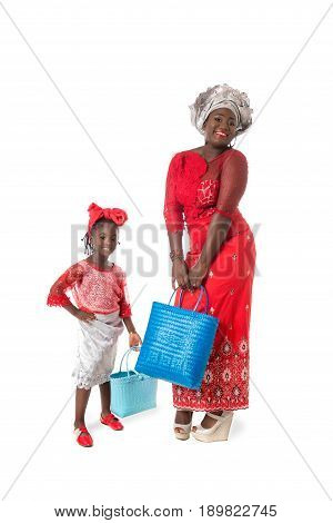 Happy African woman and little girl in traditional red clothing with bright blue wicker tote bags. Isolated on the white studio background