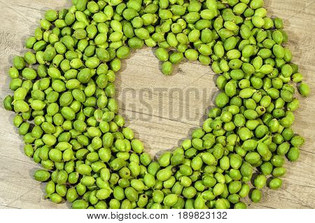 A lot green young walnuts in husks in the shape of heart on kitchen table