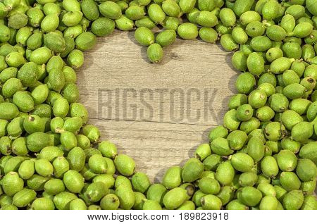 A lot green young walnuts in husks on table in the shape of heart