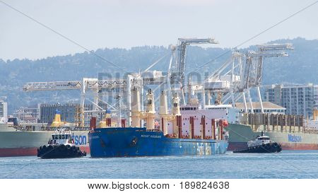 Oakland CA - June 01 2017: Tugs move vessels that should not move themselves such as ships in a crowded harbor. Multiple tugboats assists MOUNT HIKURANGI to maneuver out of the Port of Oakland.