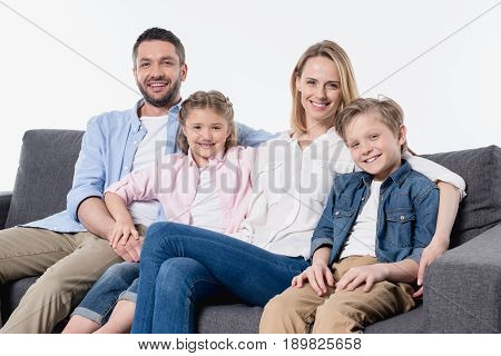 Happy Family With Two Children Sitting Together On Couch And Smiling At Camera