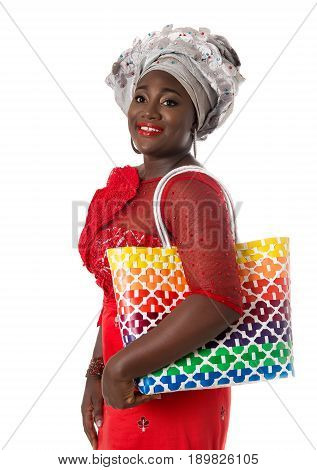 Beautiful African woman in traditional clothing with bright wicker tote bag. Isolated on the white studio background