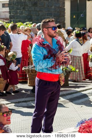 ESTREITO DE CAMARA DE LOBOS PORTUGAL - SEPTEMBER 10 2016: Man wearing in colorful costume at Madeira Wine Festival in Estreito de Camara de Lobos Madeira Portugal. The Madeira Wine Festival honors the grape harvest with a celebration of traditional local