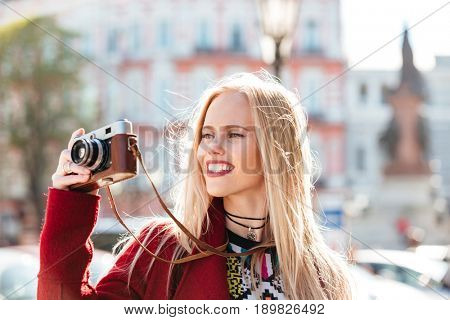 Photo of pretty young caucasian woman walking outdoors. Looking aside holding camera in hands.