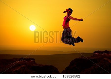 Happy joyful girl jumping against the sun and the sunset