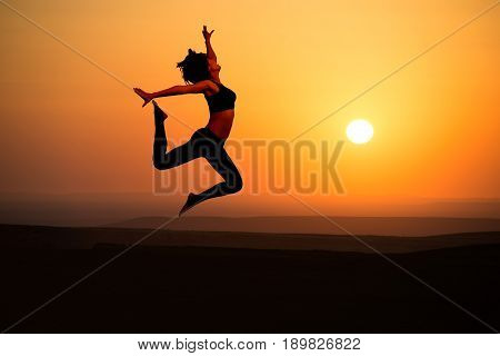 Young woman dancer on outdoor unrise background.