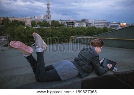 Designer with tablet is drawing on cloudy sky background. Creative woman lying on the building's roof in city during work. Blogger, distant work, wireless internet , art profession concept