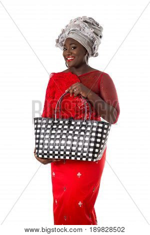 Beautiful African woman in traditional clothing with wicker tote bag. Isolated on the white studio background