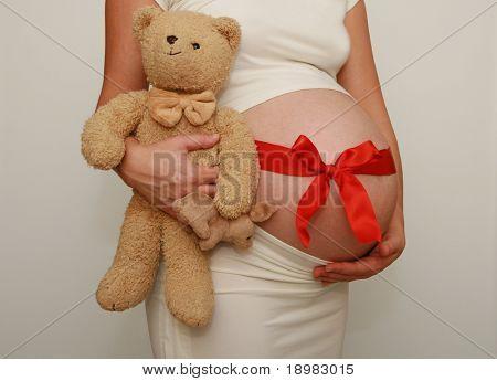 Schwangeren Bauch mit roter Schleife und süße Teddybär. Neun Monate. Dritten Trimester.