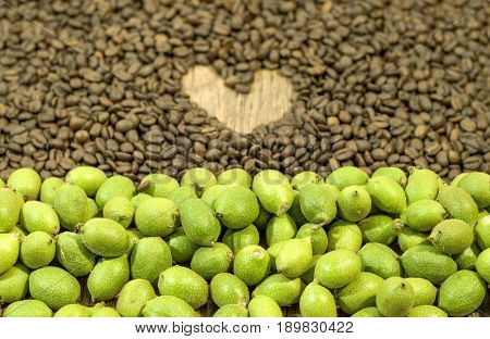 Green young walnuts in husks in front and in the back coffee benas with heart on wooden table