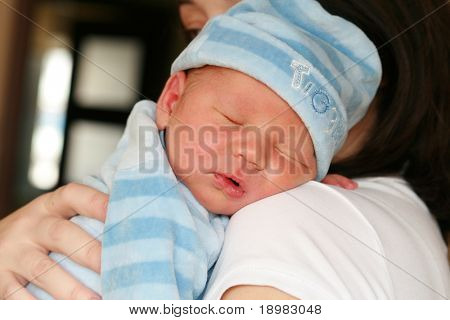 Newborn baby sleeping on her mothers arms.