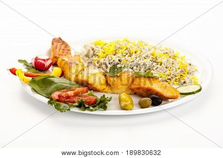 Grilled salmon kebab on plain plate with rice herbs and salad. Low angle studio shot on white tabletop. Fusion cuisine concept for healthy eating rich in n-3 long-chain polyunsaturated fatty acids.