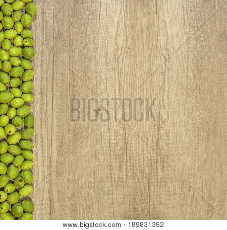 Green young walnuts in husks on the left side in row on wooden table