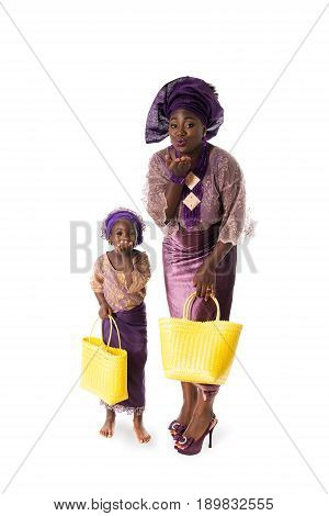Beautiful African woman and little girl in traditional purple clothing with yellow wicker tote bags showing air kiss. Isolated on the white studio background