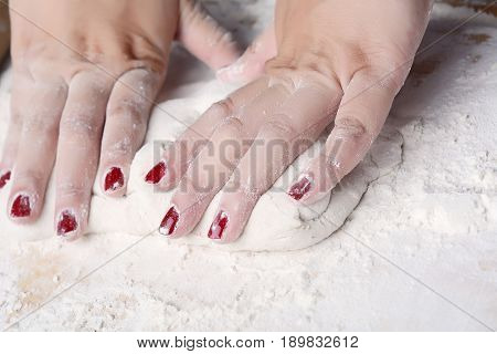 Close-up of woman hands kneading dough on wooden table. cooking and baking concept.