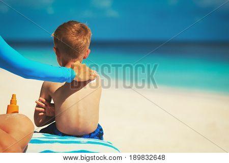 mother applying sunblock cream on child shoulder on beach