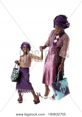 Beautiful African woman and lovely little girl posing in traditional purple clothing with wicker tote bags. Isolated on the white studio background