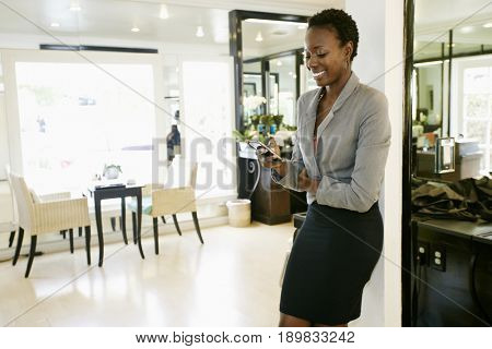 African American woman using cell phone in salon